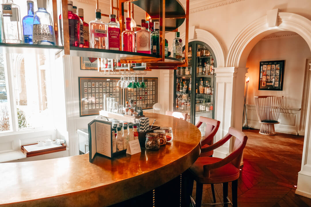 Curved brass bar at Slaughters Manor House Hotel, a luxury boutique hotel in The Cotswolds