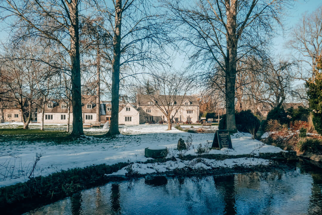 The gardens of Slaughters Inn covered in snow in the Cotswolds
